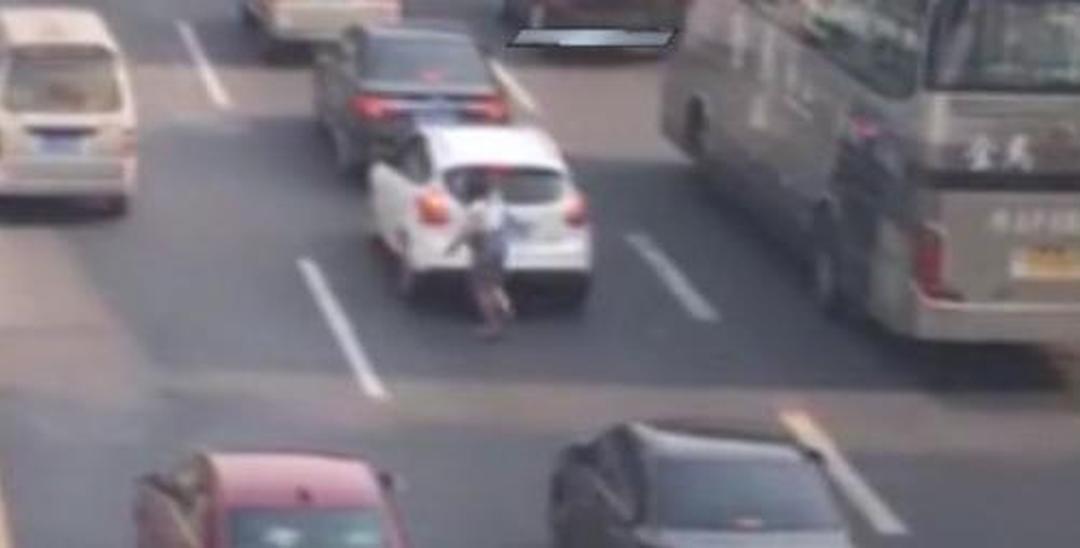 女子拿铁棒在马路上追车砸 专砸白色车和出租车
