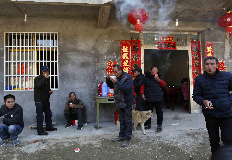 2017年2月12日,安徽省岳西县, 一位女孩出嫁,多位光棍前来喝喜酒。/视觉中国