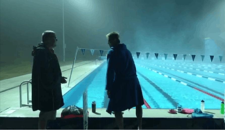 宁泽涛与布朗教练交流后准备脱掉浴袍下水训练。