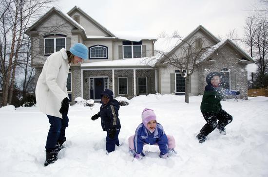 2010年12月17日,Emily Fletcher(左一)和自己的孩子在家中玩雪,Sevil(左二)是她收养的海地孤儿。/AP