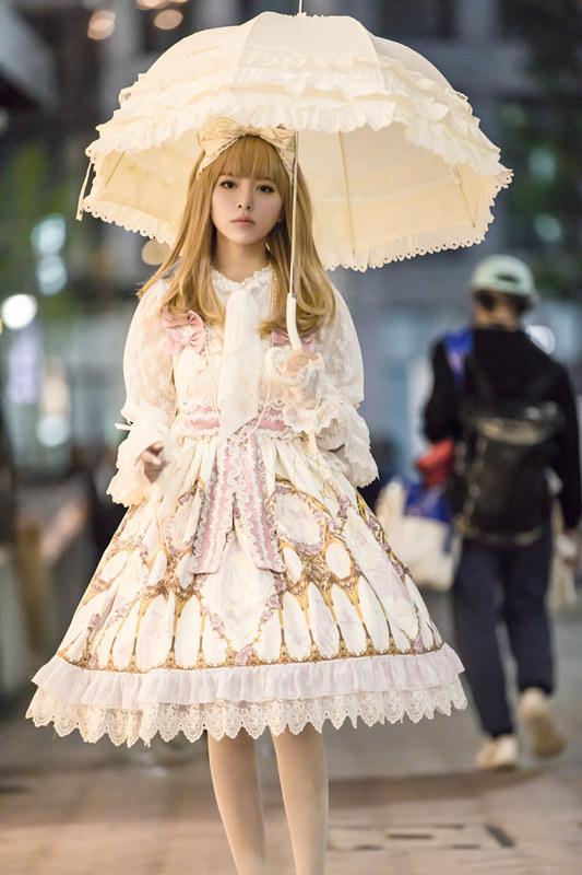 照片中,阿兰身穿田园风格的洛丽塔服,上半身粉红色的蝴蝶节与蕾丝花边