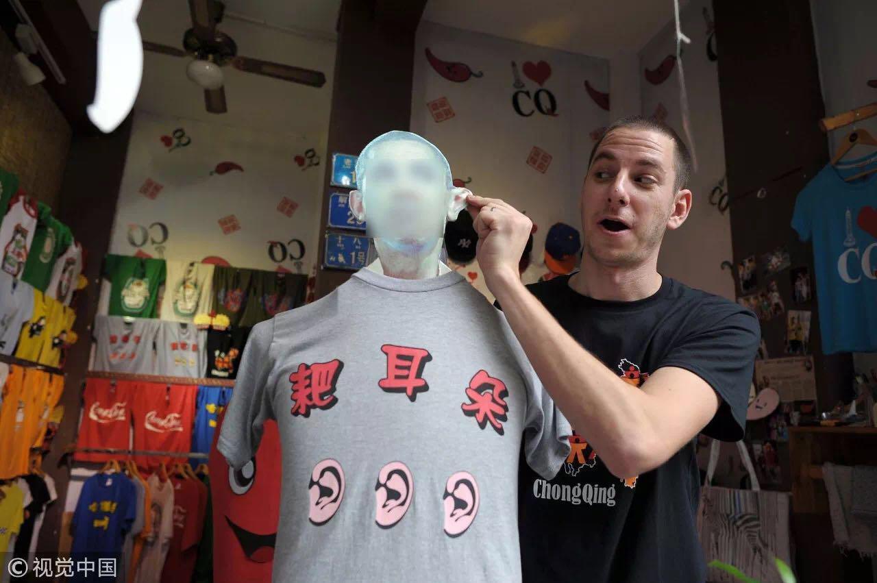 """一名来自美国纽约的29岁小伙在店里卖印有""""耙耳朵""""的T恤,他是个重庆女婿 / 视觉中国"""