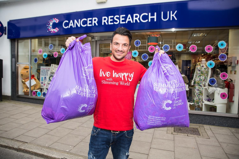 """志愿者在""""英国癌症研究""""的旧衣店门口与收集到的旧衣合影。/Slimming World"""