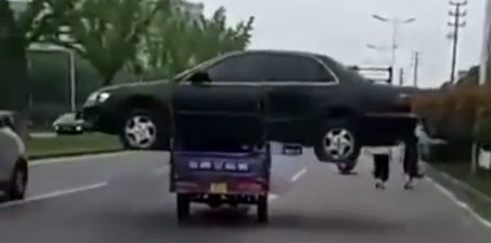 """最牛操作!男子嫌拖车运费高 竟开三轮""""扛""""轿车"""