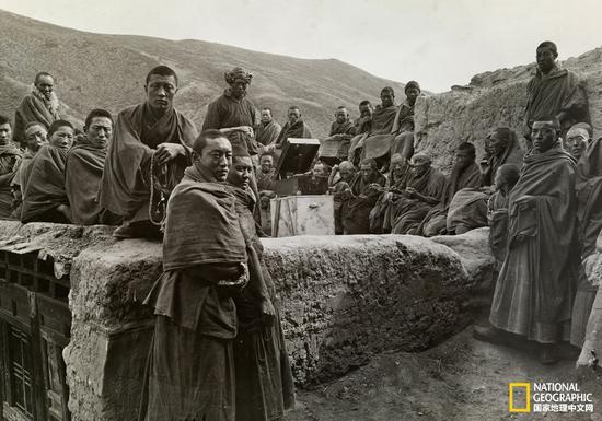 一群僧侣在探险队下塌处的屋顶,可以看到洛克随身携带的留音机(国家地理中文网2015年10月)