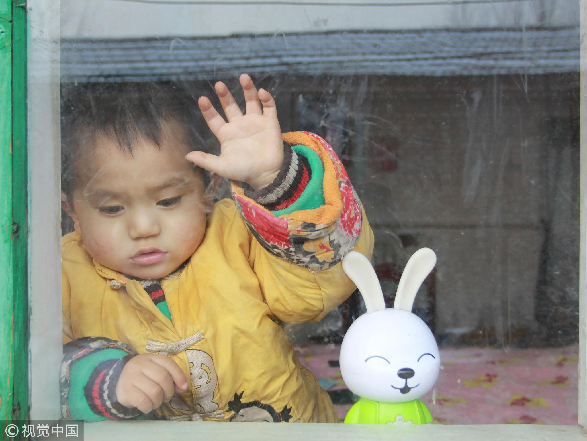 2015年1月25日,山东德州,2岁半儿子患眼癌急需治疗费用,父亲欲借钱渡难关。/视觉中国