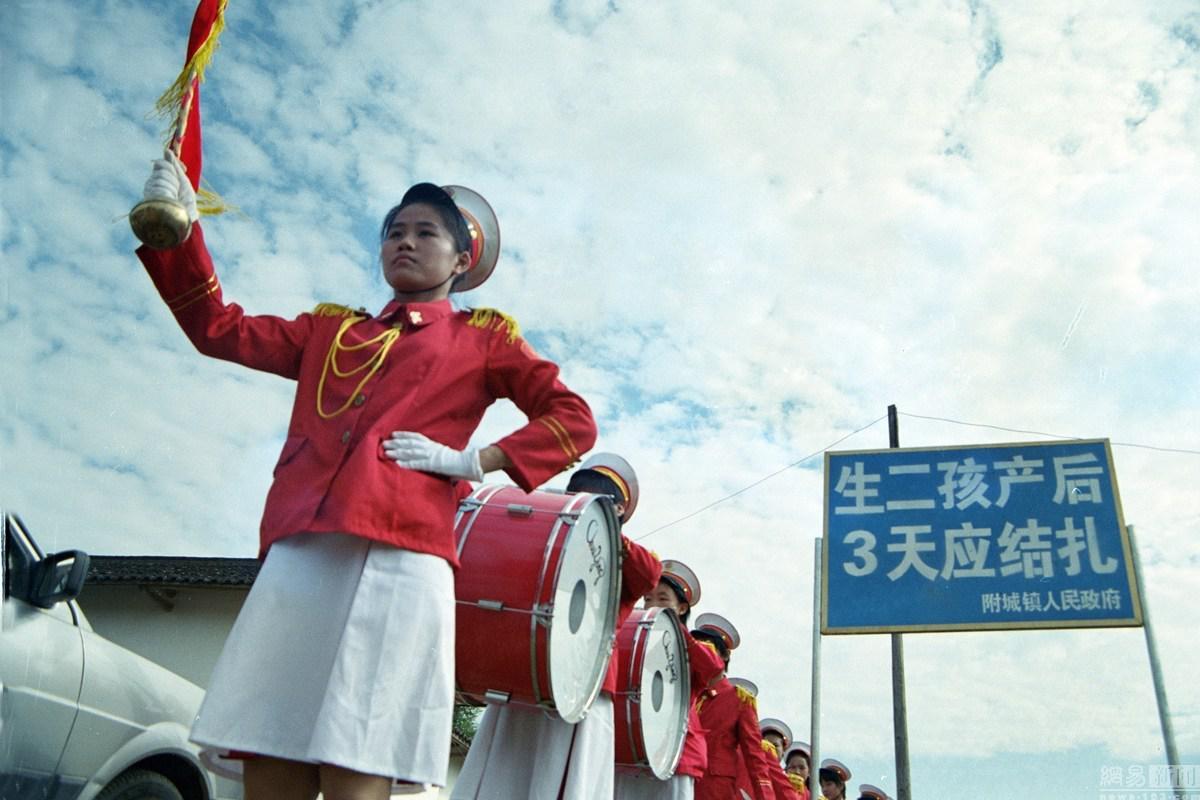 广东河源市和平县,乐队路过一块计划生育宣传牌/视觉中国