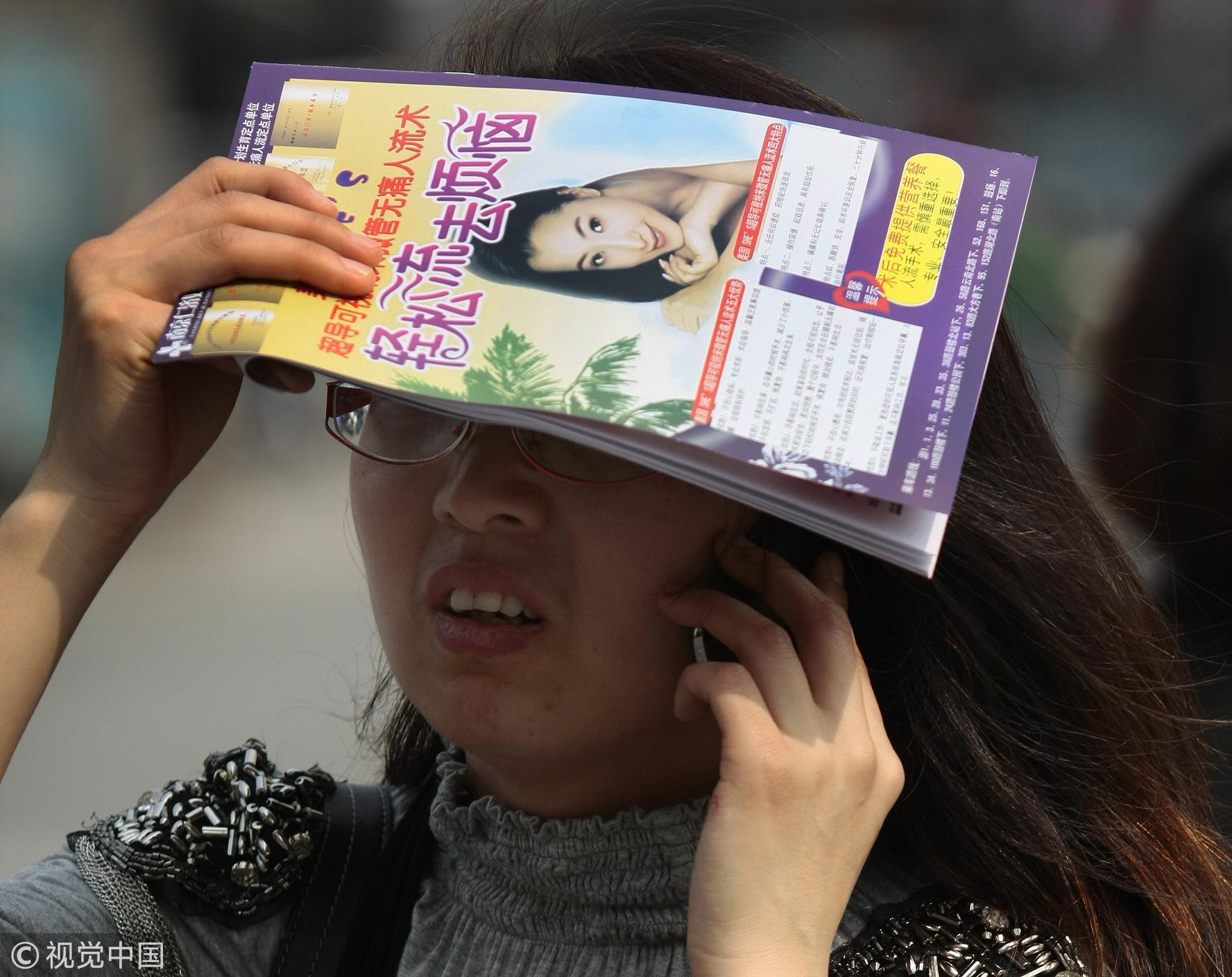 2018-06-22,南京街头手拿妇科医院人工流产手术宣传单的女士/视觉中国