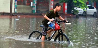 暴雨致广西街道被淹 小孩奋力踩单车