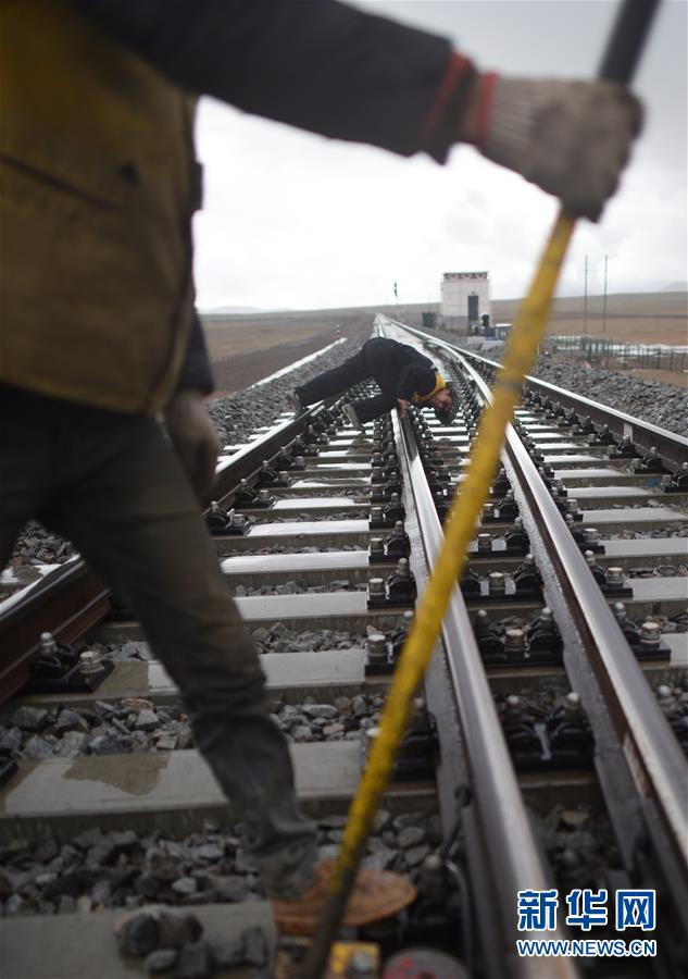 6月30日,青藏铁路唐古拉站附近,青藏集团公司格尔木工务段唐古拉线路车间主任李彪林(后)检查路轨维护状况。新华社记者张宏祥摄