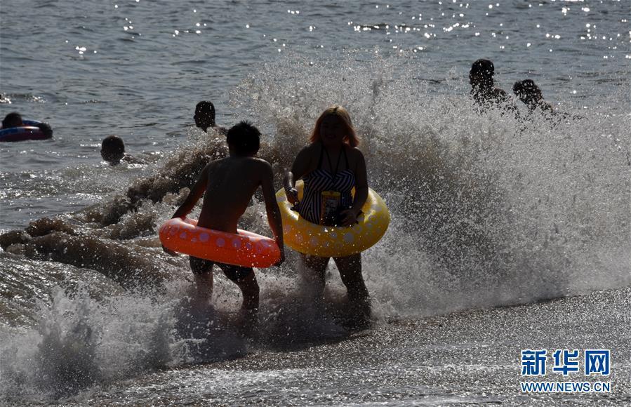 7月1日,游客在青岛第一海水浴场戏水。 新华社记者 李紫恒 摄