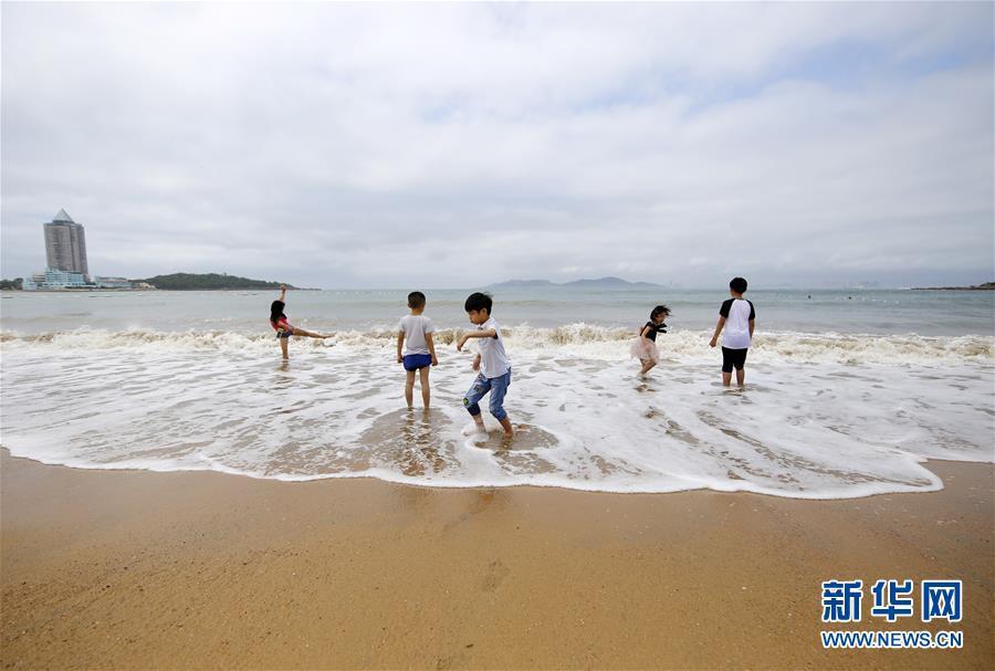 7月1日,游客在山东省青岛市第一海水浴场戏水。 新华社发(黄杰显 摄)