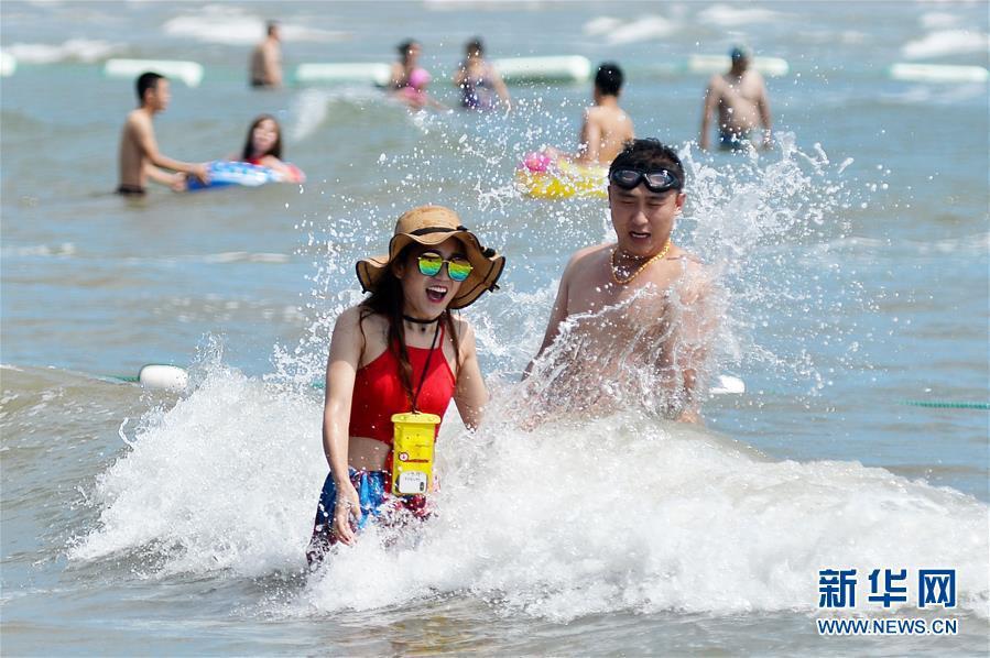 7月1日,游客在山东省青岛市第一海水浴场戏水。 新华社发(王海滨 摄)