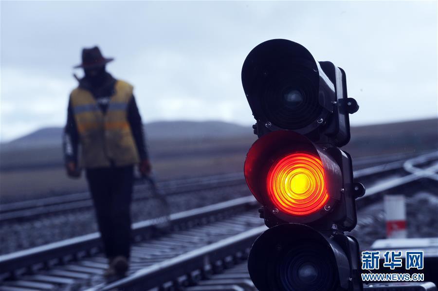6月30日,一名养路工人经过青藏铁路唐古拉站。新华社记者侯德强摄