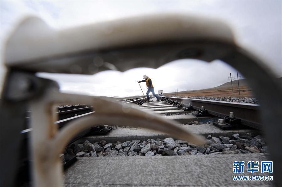6月30日,一名养路工人在青藏铁路唐古拉车站附近进行路轨养护作业。新华社记者侯德强摄