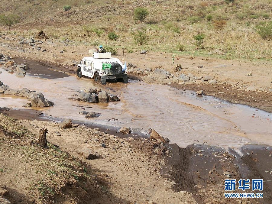 6月25日,在苏丹达尔富尔格洛,中国第14批赴苏丹达尔富尔维和工兵分队士兵驾车通过河道。中国第14批赴苏丹达尔富尔维和工兵分队7月4日在路况恶劣、安全局势严峻的情况下,顺利完成格洛临时作战基地至塔维拉维和营地之间的105公里道路勘察任务,并提交了详细报告。新华社发