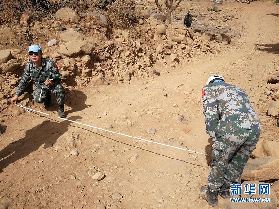 5月27日,在苏丹达尔富尔格洛,中国第14批赴苏丹达尔富尔维和工兵分队士兵在对碎石路面进行测量。中国第14批赴苏丹达尔富尔维和工兵分队7月4日在路况恶劣、安全局势严峻的情况下,顺利完成格洛临时作战基地至塔维拉维和营地之间的105公里道路勘察任务,并提交了详细报告。新华社发