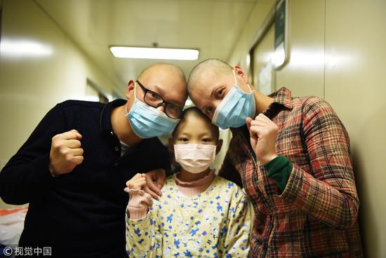 2017年12月26日,郑州。10岁女童突发白血病,父母剃光头鼓励。做化疗,不掉头发是不可能的。/视觉中国