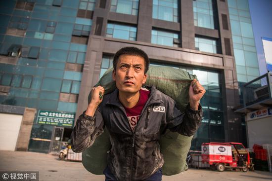 2017年11月4日,河北廊坊。为救白血病女儿,男子扛包攒钱,偷偷吃馒头咸菜。中国有太多的人看不起大病了。/视觉中国
