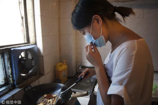 2014年7月18日,长沙。白血病患者免疫力低下,所以在蒸笼一样的厨房里,依然要戴口罩做饭。/视觉中国