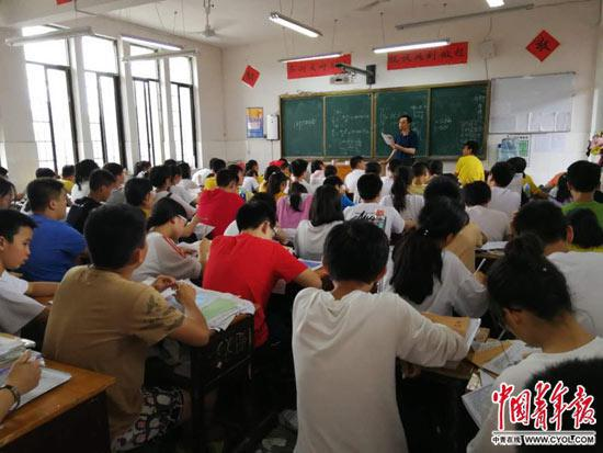 6月14日,新化县上渡街道办事处明德学校初中部的学生在上课,这个班的学生94人,老师需戴麦克风上课