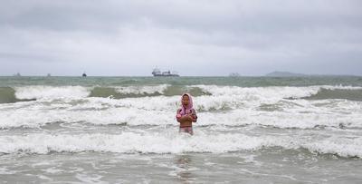 """台风山神""""横穿""""海南 游客不惧风雨海边嬉水"""