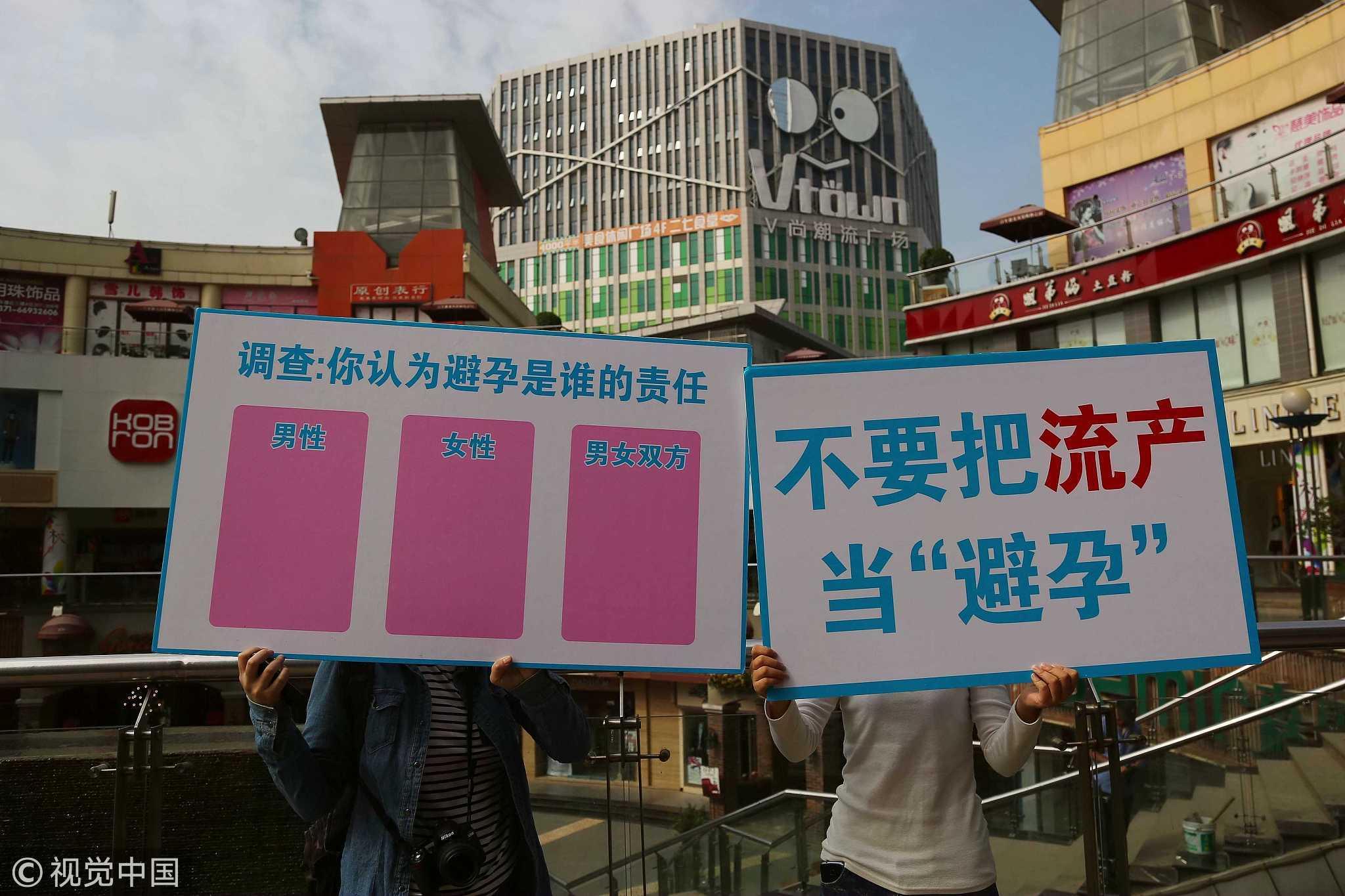 2018-10-18,郑州市二七广场,三名女子举着牌子宣传:不要把人流当避孕。 / 视觉中国