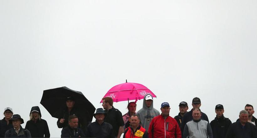 英国公开赛阴雨绵绵 选手撑伞观赛