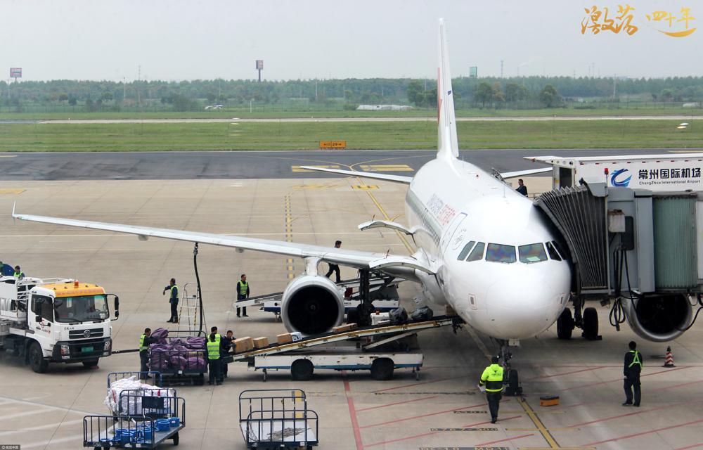 机场地勤人员正向航班飞机腹舱输送物流快件包裹。  图片来源:视觉中国
