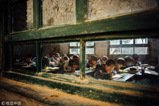 2015年3月,甘肃天水。孩子们在没有灯的教室里就着晨光学习,教室外就是甘肃的大山,窗户映出了土黄色。 / 视觉中国