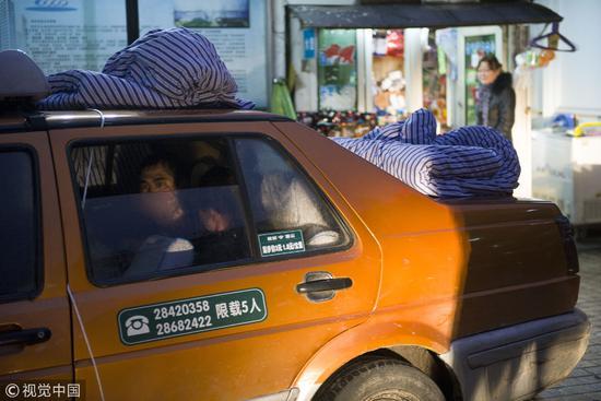 2013年2月20日,湖南株洲某医院,一位被狗咬后未经处理的狂犬病人,确诊后,家人用绳子将他捆住,并用棉被裹住,送上的士准备送回家乡 / 视觉中国