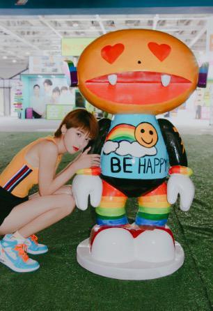 """芒果崽身穿点缀有彩虹白云,笑脸太阳和""""be happy""""字样的蓝色t恤,并配"""
