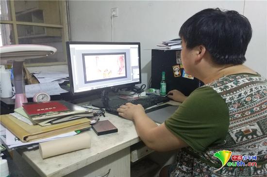 汤晓艳正在电脑上进行美术创作。费雷 摄