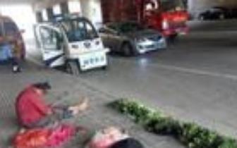 郑州街头一大娘卖菜时睡着,城管在一旁默默守护