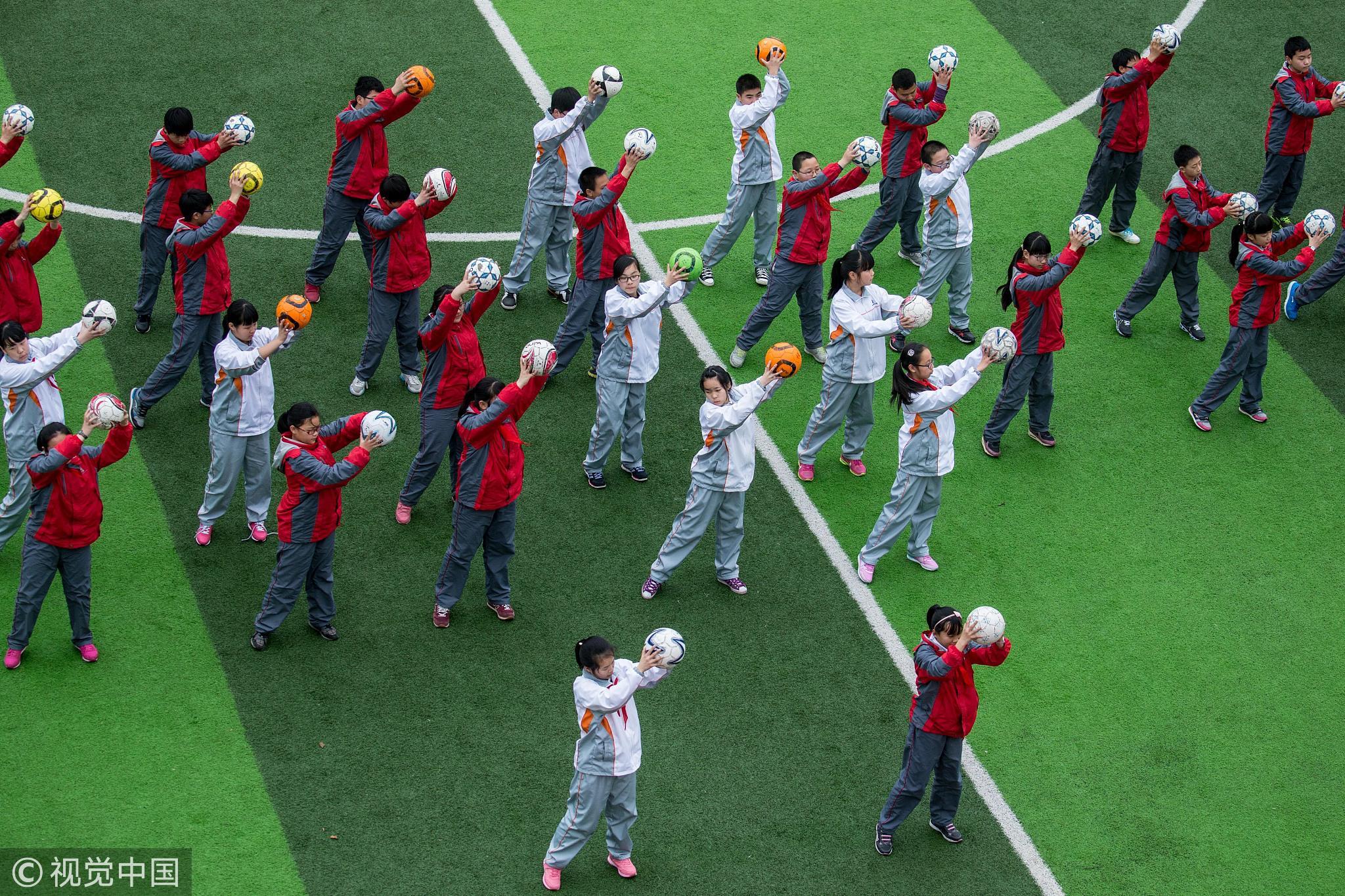 2015年3月18日,浙江杭州启航中学的学生抱着足球在体育课上跳操热身,这样玩足球,可能只有中国体育老师能想得到/视觉中国