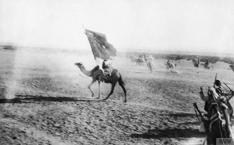一名起义军骑兵举着旗帜冲向亚喀巴