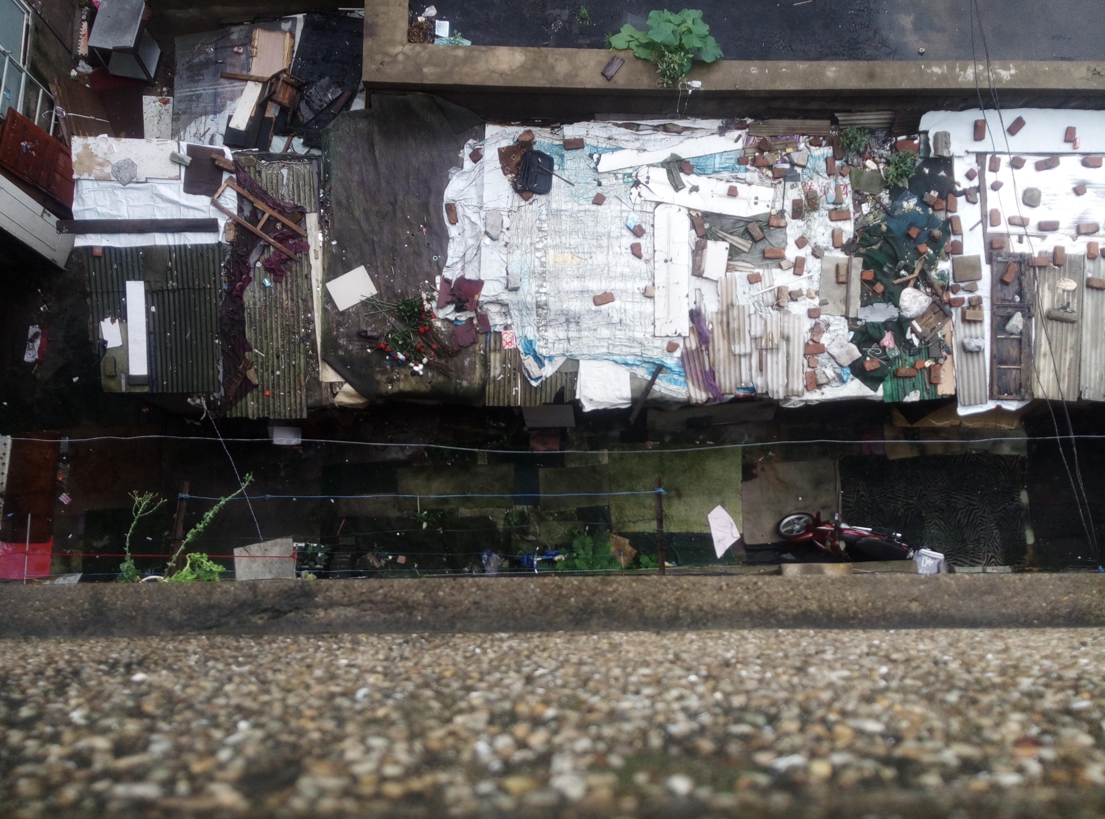 在五楼俯瞰时的一楼内院,棚屋挡得铺了纸壳的小路很窄。 (作者供图)