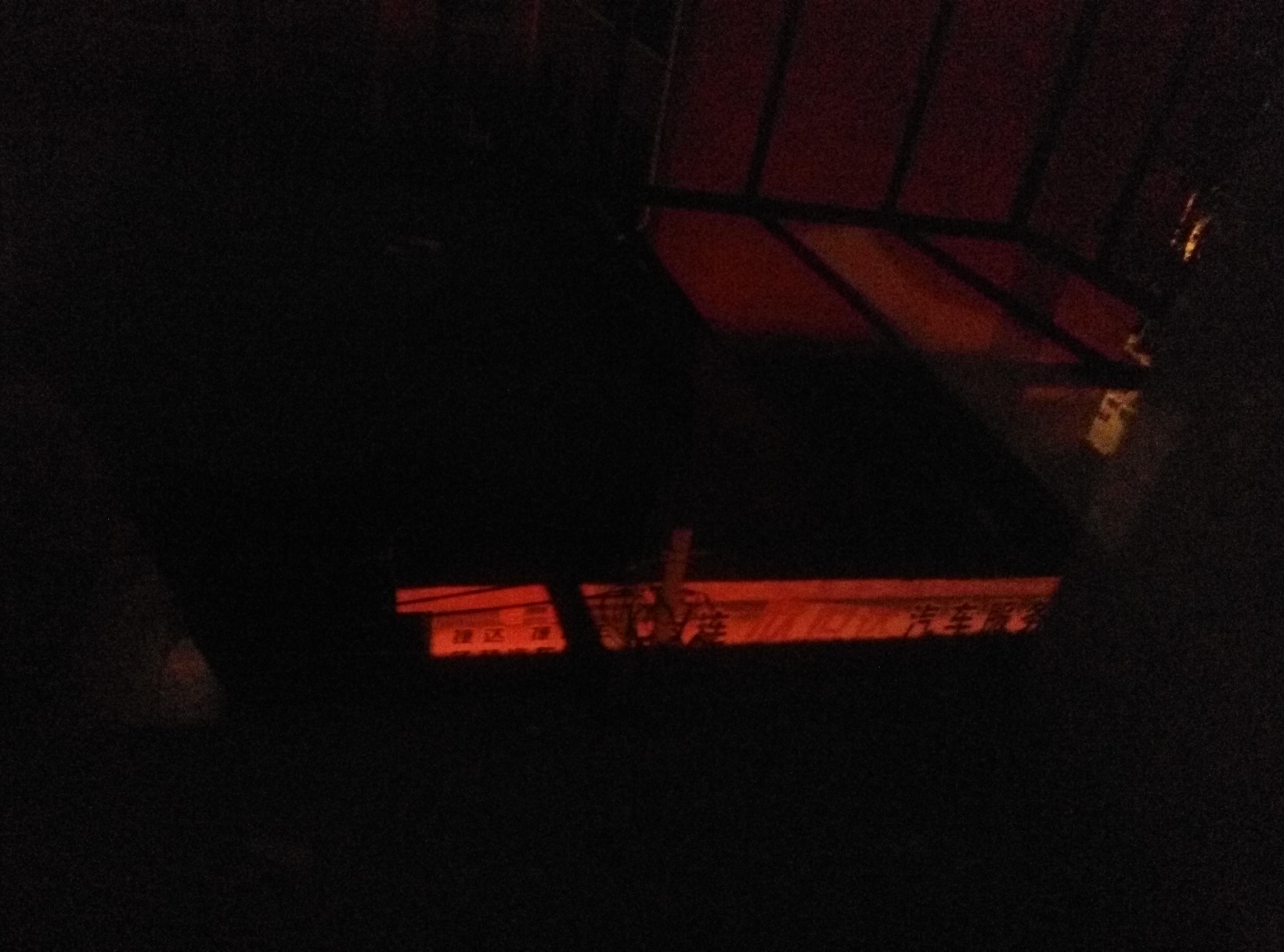 从屋里窗户缝隙拍到的楼下的红光,11号阿姨说的女人就等在这条街上。 (作者供图)