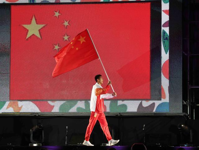 中国代表团旗手王云章在开幕式上高举国旗入场