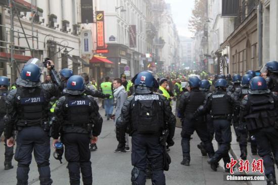 资料图:当地时间11月24日,巴黎香榭丽舍大街遭遇大规模示威活动。数以千计示威者聚集在街上,设置了不少路障,街道交通完全陷入瘫痪。图为法国警方当天在香榭丽舍大街附近与大批示威者对峙。中新社记者 李洋 摄