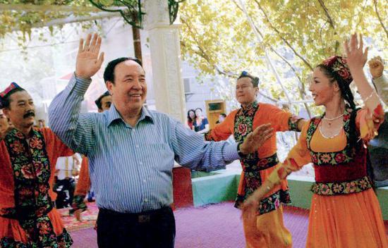 2006年9月26日,全国人大常委会副委员长司马义·艾买提来到新疆吐鲁番葡萄沟乡与新疆维吾尔兄弟共舞,庆祝新疆维吾尔自治区成立五十周年。图/中新
