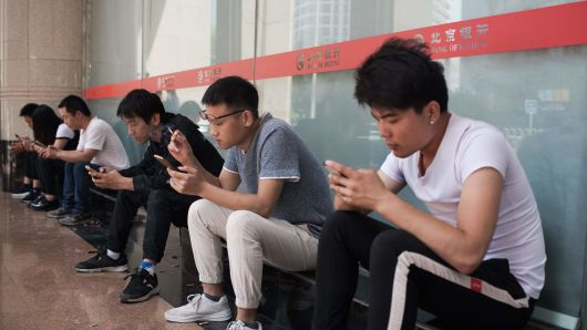 People use their mobile phones outside an office building in Beijing on May 24, 2018.?