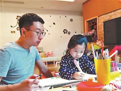 江涛陪着已经5岁的女儿画画