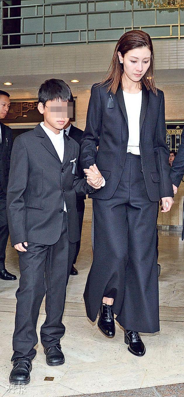 李嘉欣牵着7岁儿子许建彤步出殡仪馆,神情哀伤,眼睛鼻子通红