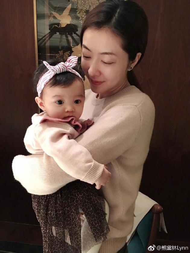 辣妈熊黛林怀抱女儿满眼爱意 小宝贝却专注看别处
