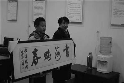 """陈锦芳老人特意请书法家写了幅""""书海赋春""""赠送给桂天生。校方供图"""
