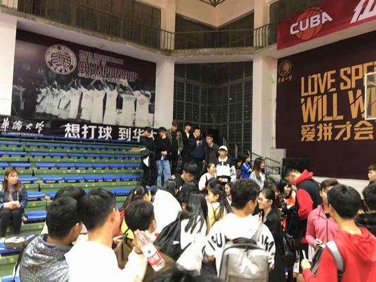 华大现役球员孟翔(画面中间低头签名者)赛后被同学团团围住