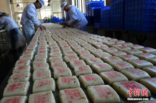 资料图:师傅们在把制作好的桂花糖年糕摆放整齐。王思哲 摄