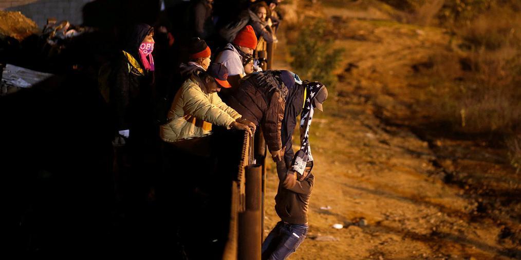 中美移民翻越美墨边境墙遭持枪警告