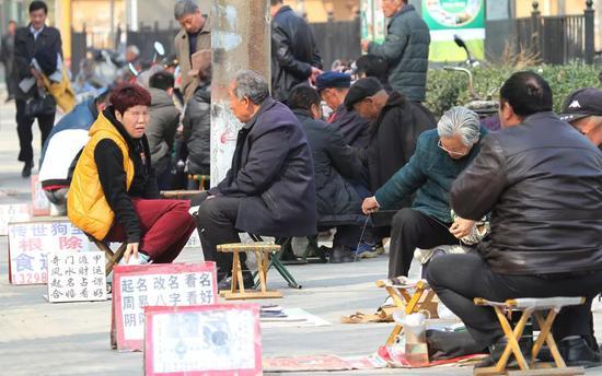 """郑州儿童公园的""""算命小市场"""",本质上看相算命大师跟星座大师都是江湖骗子/视觉中国"""